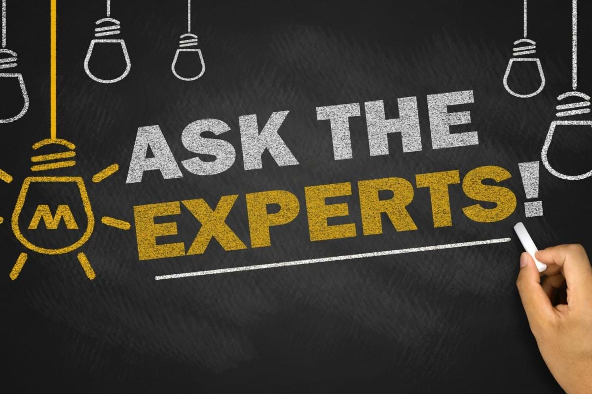 "The words ""Ask The Experts"" drawn on the chalkboard, along with light bulbs"