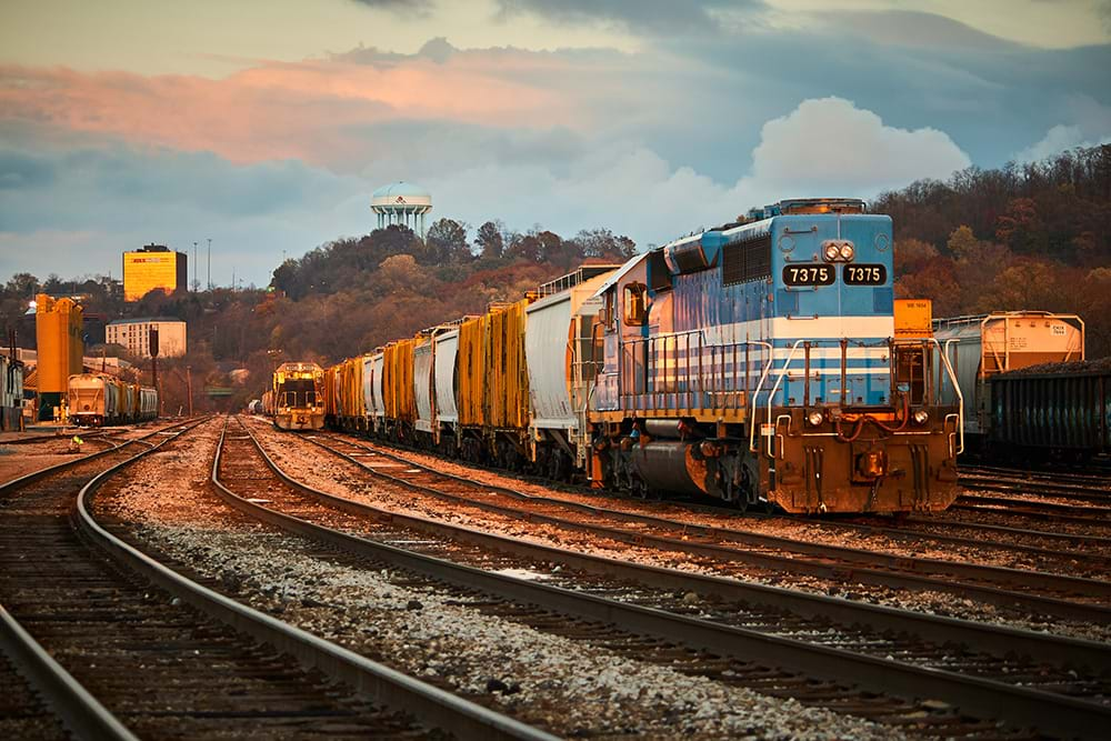 A parked locomotive and a line of railcars at a storage yard at sunset