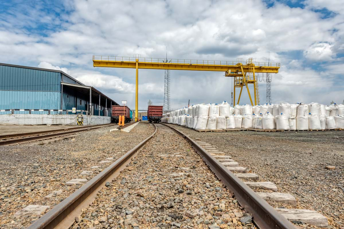 An industrial warehouse with numerous big bags of bulk substance being transloaded by a gantry crane to two railcars