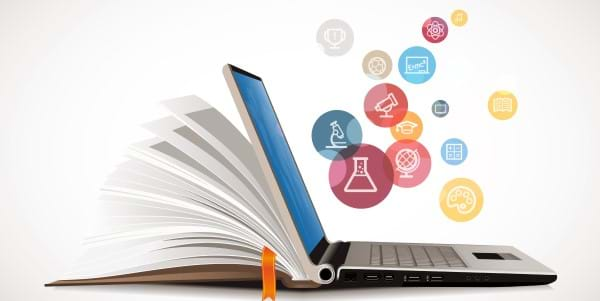 An open laptop on the right and an open book on the left, with colorful knowledge bubbles floating above the laptop