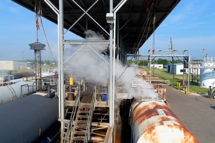 Tank-style railcars undergoing a steaming treatment as an initial part of the railcar cleaning process