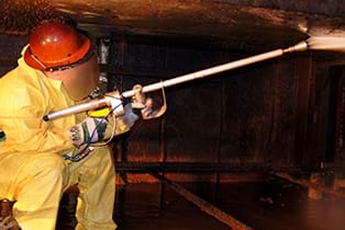 A worker covered in safety gear is using a high-pressured water jet to remove hardened materials from a rail car