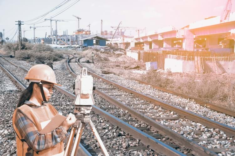 A female engineer using rigorous surveying techniques to analyze railway tracks