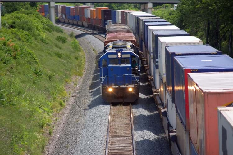A locomotive performing railcar switching by pulling a short train beside parked intermodal cars