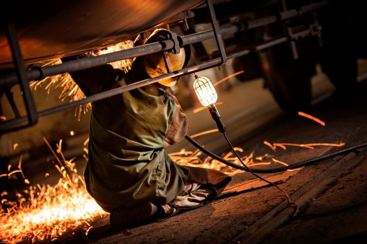 A Welder on the floor of a railcar repair shop welding the underside of a tank car