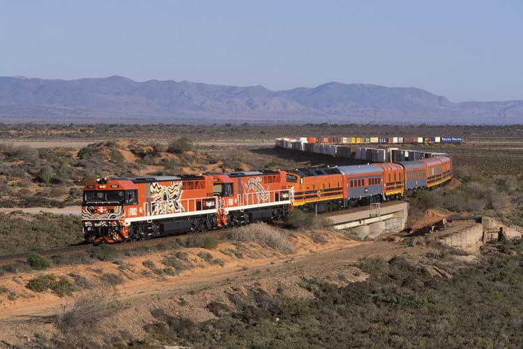Freight train painted in bright orange with intricate designs, traveling across rural landscape