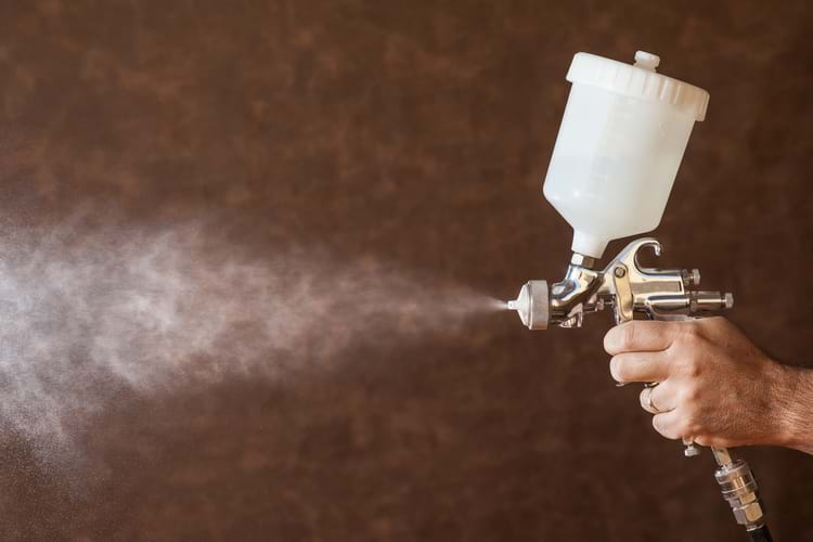 Close up of a spray paint gun spraying atomized paint into the air