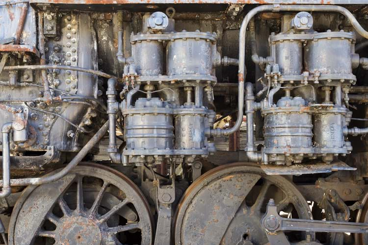 Details of an old steam train engine with rust and damage