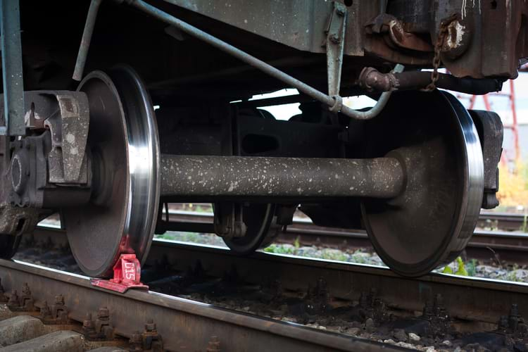 A red railway brake shoe under the train wheel on the rails