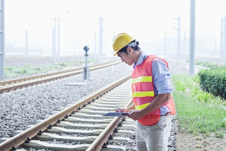 A railroad worker in protective work gear checking the railroad tracks