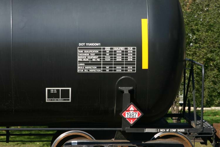 Tank car qualification stencil with black background and white grid & lettering