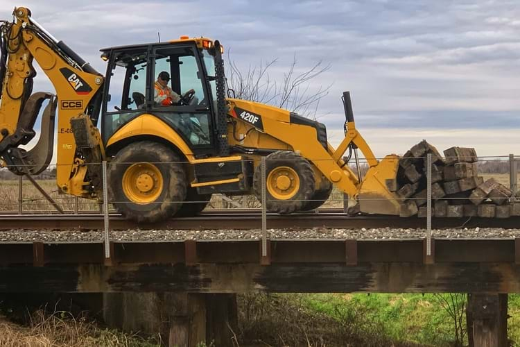 A railroad worker driving a back loader, pushing railroad ties on top of the railroad track