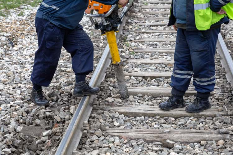 Railroad track workers removing clips from the railroad tracks using a vertical vibration tamper