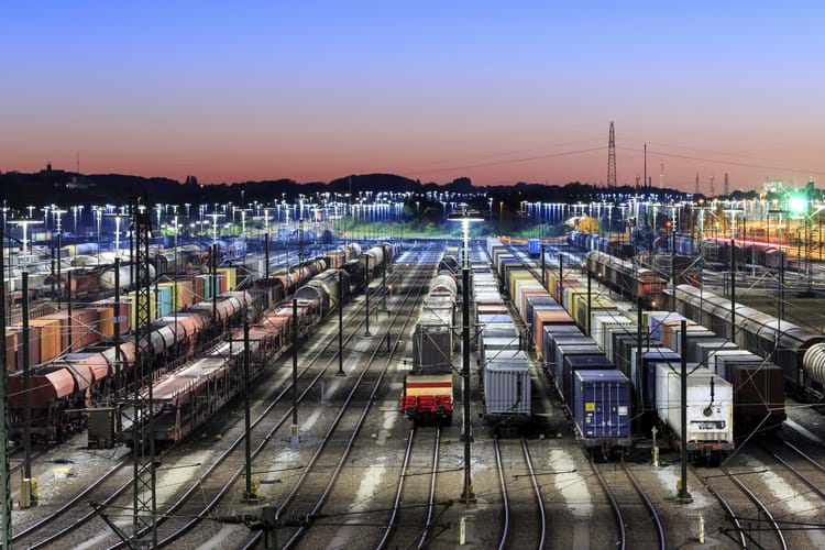 Many different railcars stored at a brightly lit storage yard