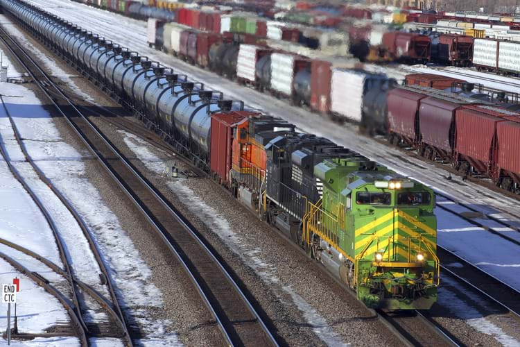 A railcar storage yard covered with snow with different types of freight cars