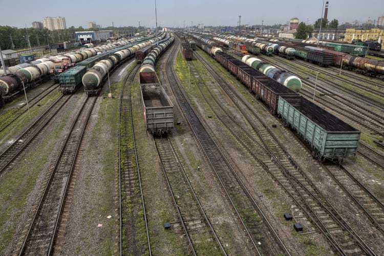 A storage yard with lots of railroad tracks and freight trains during daylight