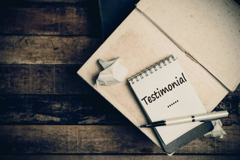 Testimonial Word on Sketch Book on Wood Table