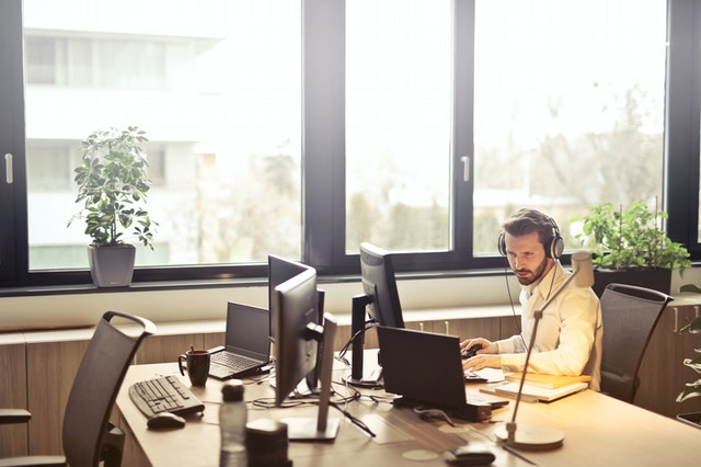 Man With Headphones Facing Computer Monitor 845451